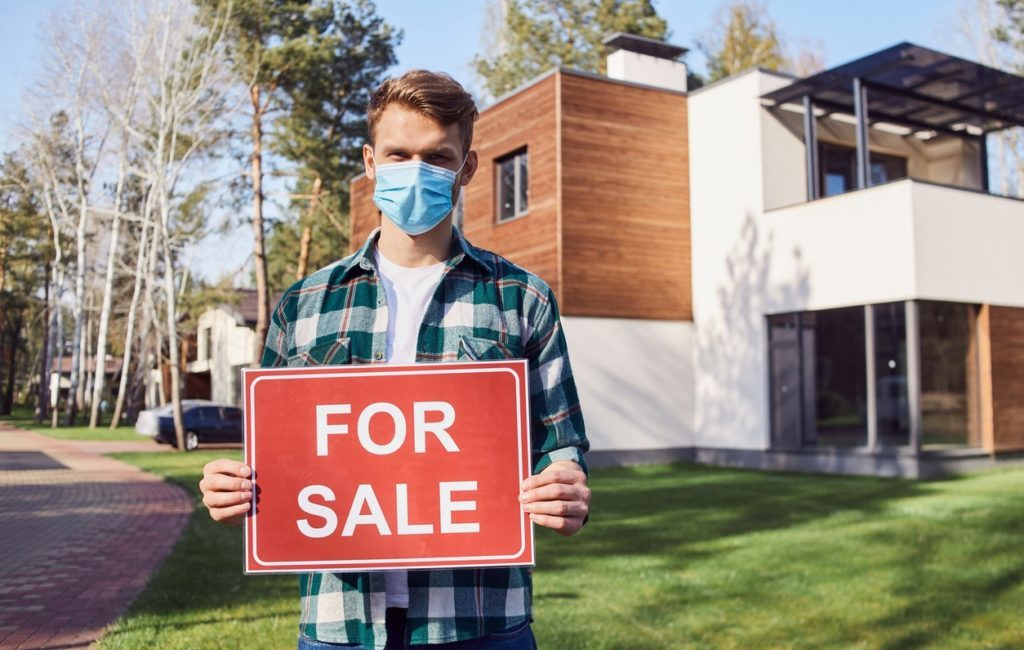 Man holding For Sale sign in front of house